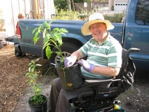 man in wheelchair holding a plant
